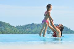summer vacations concept. happy mother and daughter playing in blue water of  - stock photo