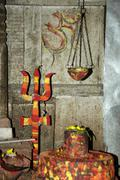 Stock Photo of shrine for god shiva with a lingam and trisul red yellow and orange coloured