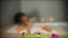 Woman relaxing in bubble bath with champagne blurred Stock Footage