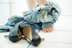 young woman taking off dirty worn-out jeans in the bathroom - stock photo