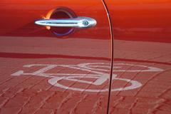 Red car door reflecting a pictogram from a bicycle lane Stock Photos