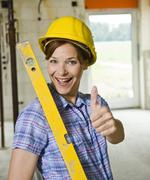 craftswoman with hard hat and level giving a thumbs up - stock photo