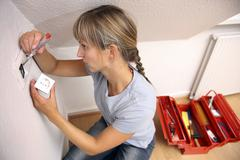 young woman installing a power socket - stock photo
