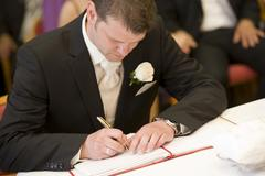 groom signing marriage certificate at the registry office - stock photo