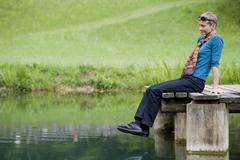 Lady, 60 plus, sitting on a jetty at a pond Stock Photos