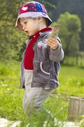 young boy, 18 months, playing in the garden - stock photo