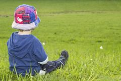 Young boy, 18 months, sitting in a meadow and enjoying the view Kuvituskuvat