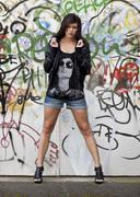Young woman with dark hair wearing hot pants, a black leather jacket and high Stock Photos