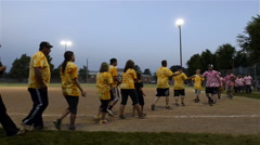 Opposing teams giving high 5's after annual coed softball game Stock Footage