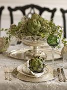 artichoke on fine china in a luxurious ambience - stock photo