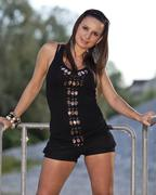 young woman wearing a black top and hot pants posing, standing in front of ra - stock photo