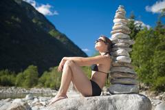 woman in bikini next to a stone pyramid, valle verzasca, tessin, switzerland, - stock photo