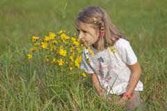 Little girl smelling flowers Stock Photos