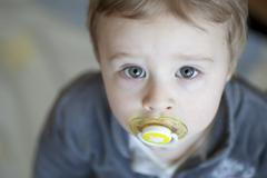 young boy, 18 months, with a pacifier in his mouth, portrait - stock photo