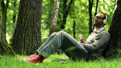 Young man listen to music on smartphone in the park HD Stock Footage