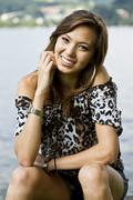 young woman wearing hot pants and a leopard-print top, sitting, smiling - stock photo