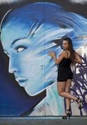 young woman wearing hot pants and high heels posing in front of graffiti wall - stock photo