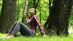 Young woman chilling out on grass in the park HD Stock Footage
