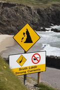 Warning signs in gaelic and english, strong currents, swimming prohibited and Stock Photos