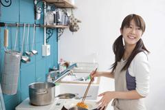 young woman working in kitchen - stock photo