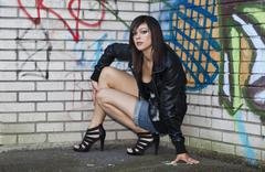 Dark-haired young woman wearing hot pants, a black leather jacket and high he Stock Photos