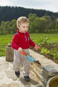 young boy, 18 months, carrying a garden shovel - stock photo