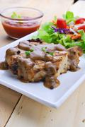 grilled steaks, pork with pepper gravy and vegetable salad - stock photo