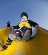 Young boy, 18 months, sliding down a slippery-dip with his mother behind him Kuvituskuvat