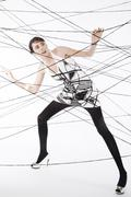 woman, 24, dressed in the style of the 60s, standing between spanned threads, - stock photo