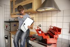 young woman repairing a toaster in the kitchen - stock photo