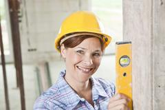 craftswoman with hard hat and level - stock photo