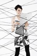 Woman, 24, dressed in the style of the 60s, standing between spanned threads, Stock Photos