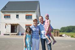 Family standing in front of their new home Stock Photos