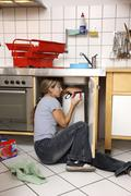 Young woman repairing a defective water faucet in a kitchen Stock Photos