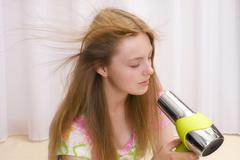 Girl, 17 years, with hair-dryer Stock Photos