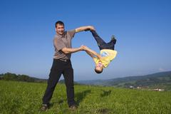 father, 36 years, and son, 6 years, playing in a meadow - stock photo