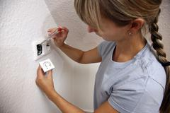 Young woman installing a power socket Stock Photos