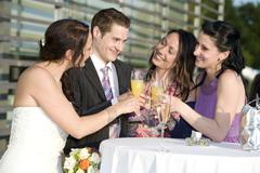 Bride and friends clinking glasses with champagne Stock Photos