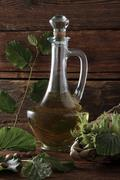 A bottle of hazelnut oil and some ripe and unripe hazelnuts (corylus avellana Stock Photos
