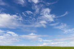 green grass and sky with clouds - stock photo