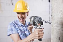 Laughing craftswoman with hard hat and power drill Stock Photos