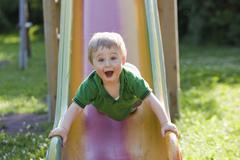 Little boy having fun on a slide Kuvituskuvat