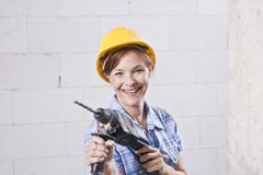 craftswoman with hard hat and drill machine - stock photo