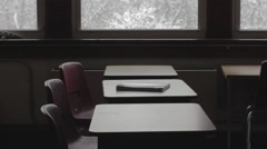 Empty classroom dolly across desks looking out windows - stock footage