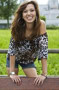 young woman wearing hot pants, a leopard-print top, smiling, leaning on back  - stock photo