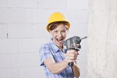 laughing craftswoman with hard hat and power drill - stock photo