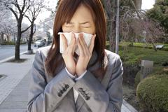 young woman sneezing - stock photo