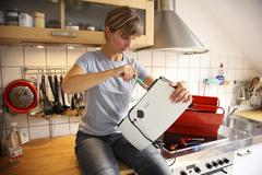 Young woman repairing a toaster in the kitchen Stock Photos