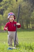 Young boy, 18 months, playing in the garden with a broom in his hand Stock Photos