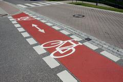bicycle path marked with red - stock photo